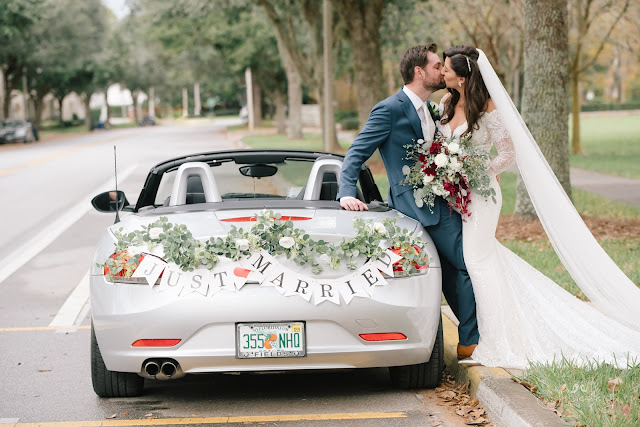 bride and groom kiss with car just married sign