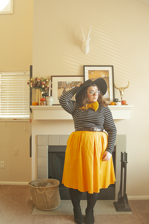 An outfit consisting of a wide brim black hat, striped mock neck shirt tucked into a yellow midi skirt, with tights and black ankle boots.