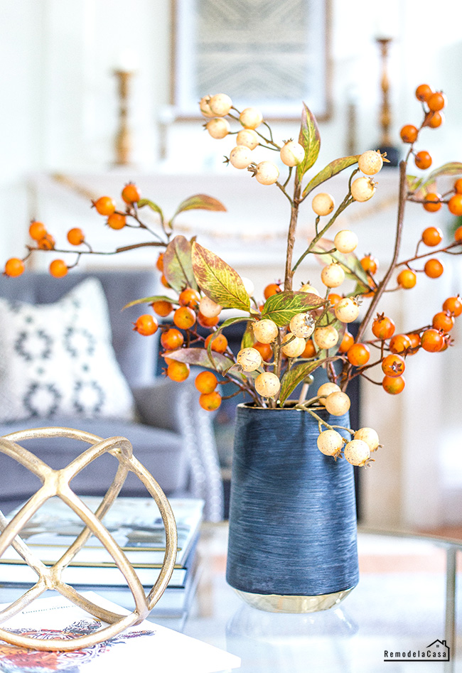 black vase with autumn berry branches and golden sphere