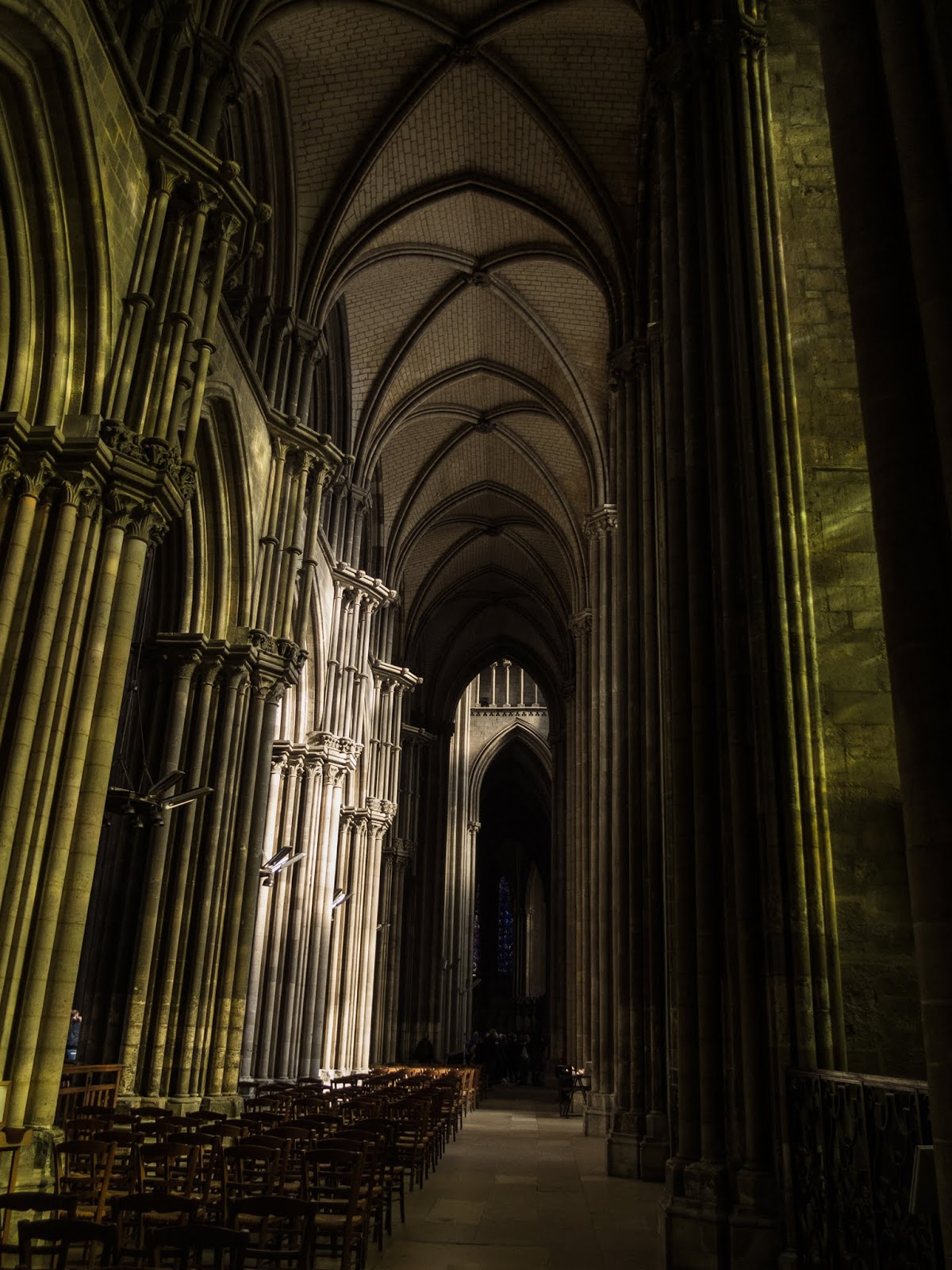 Light shining through stained glass onto the walls of the Rouen Cathedral.