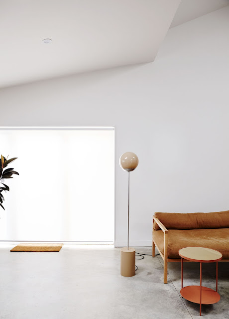 cognac brown leather sofa with simple light wood frame, modern free-standing floor lamp with wood circular base and glass globe light