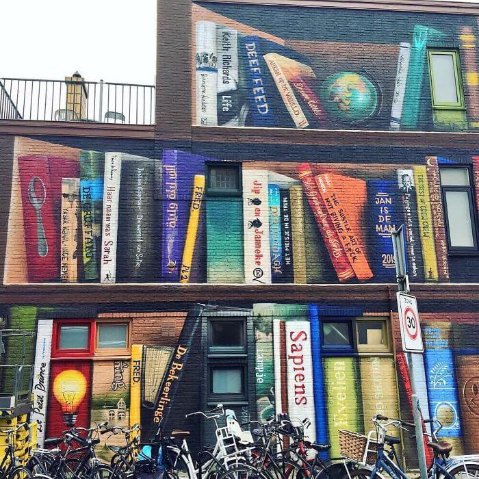 Dutch Artists Paint An Enormous Bookcase On An Apartment Building That Features Residents' Favorite Books