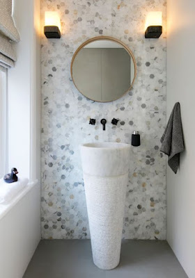Tiny hexagon tiles for unique bathroom decor with cool marble sink and round wall mirror