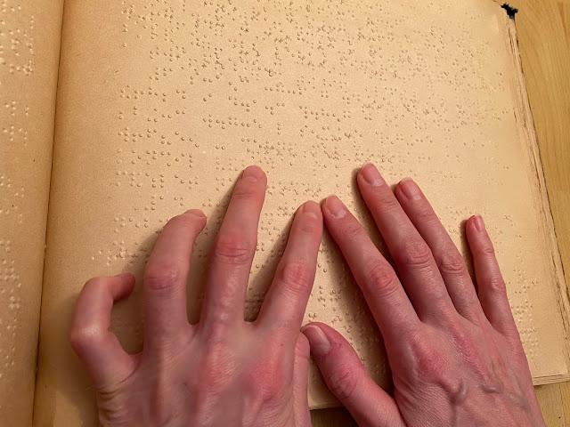 Záběr na ruce při čtení textu v Braillu
