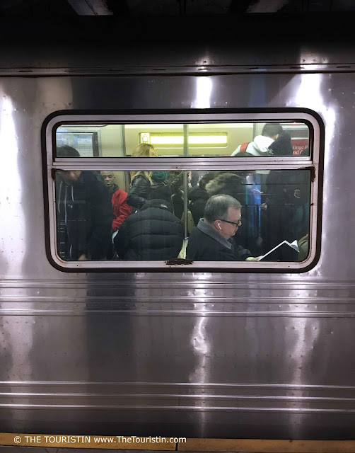 Passengers seen through the window of a silver coloured subway train in NYC