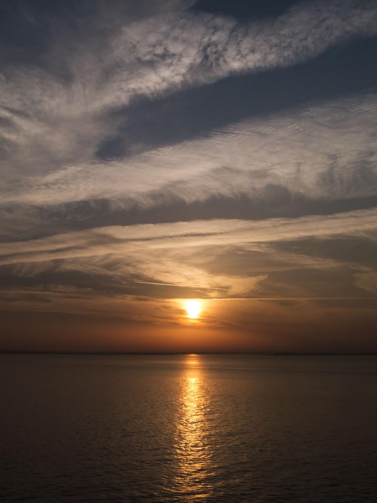 Sun risen above the horizon casting a reflection across water in Lisbon.