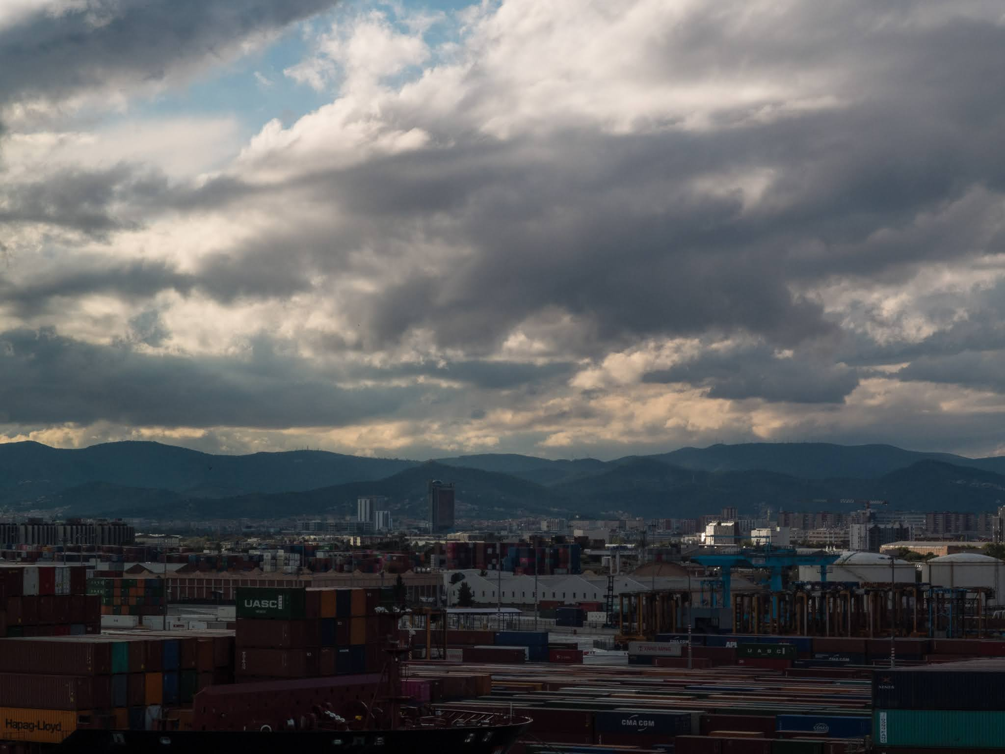 View of mountains from the port of Barcelona, Spain with containers in the foreground.