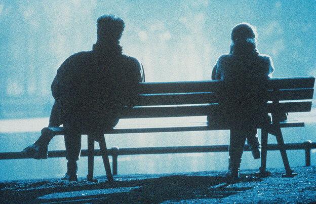 Dos personas distanciadas sentadas en una banca