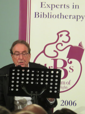 Eric Idle seated in front of Poster for Mr B's Bookshop