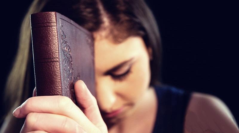 uma mulher segura uma bíblia e orar a Deus pedindo auxílio
