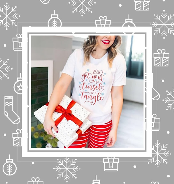 Woman holding a Christmas gift, whilst wearing a Christmas tshirt