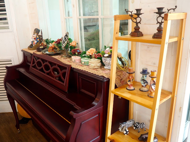 Cafe interior details - upright piano and shelves of ornaments in Marisstella cafe in Myeongnyun, Busan, South Korea