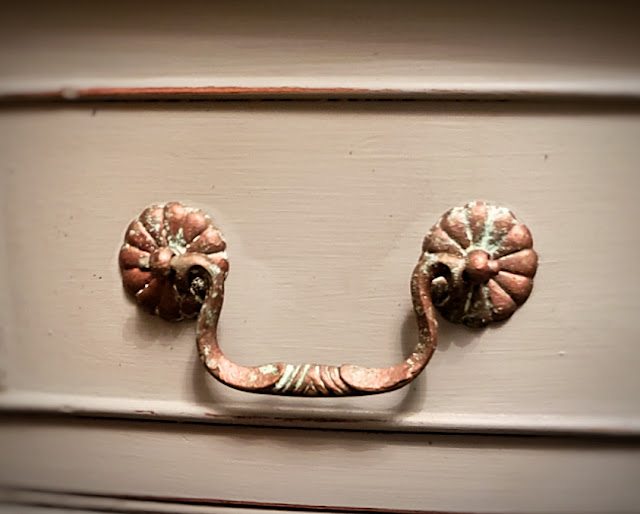 close up picture of the copper and patina handles on the front of the buffet drawer