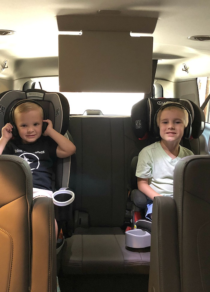 Two blonde boys in car seats smiling while they listen to headphones in a three row SUV on a road trip