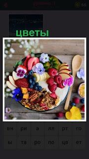 на подносе на столе лежат фрукты и вокруг находятся цветы