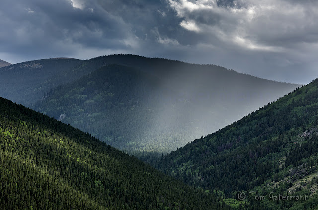 Sunlight peaks through the clouds in this view from Squaw Pass Road.