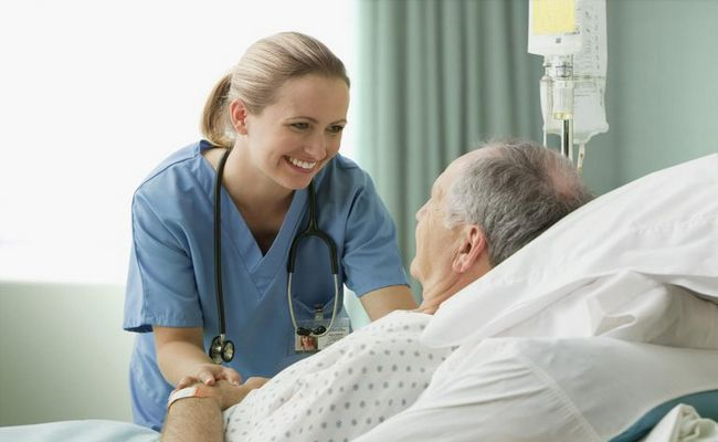 A registered nurse works with patient
