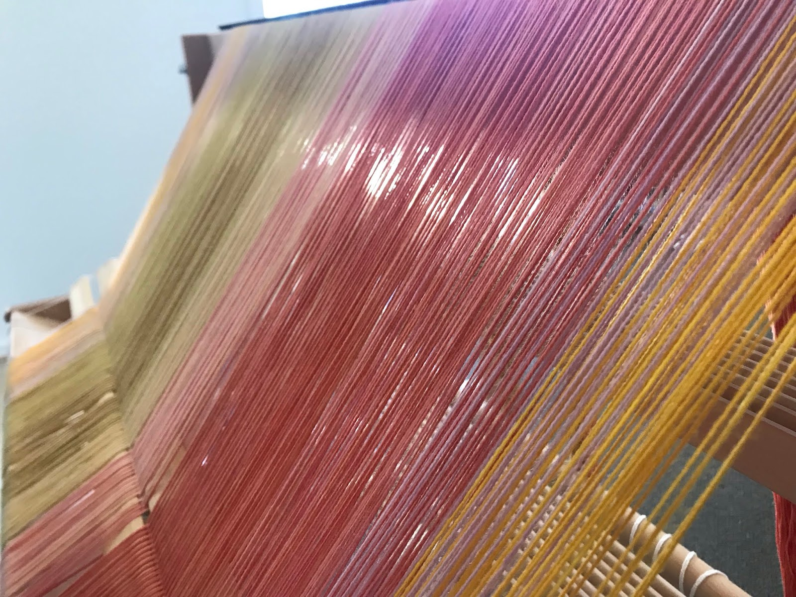 A warp going into a raddle. The yarn takes up the entire image, with pinks in the foreground and yellows in the background.