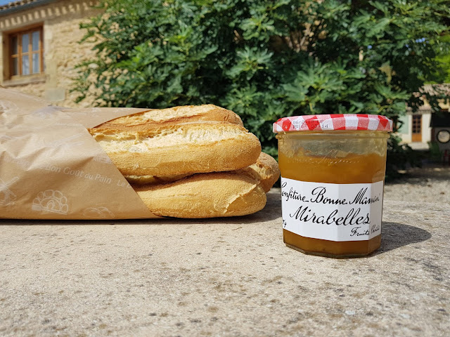 A jar of Bonne Maman Mirabelle Conserve next to fresh french bread and a gite in the background