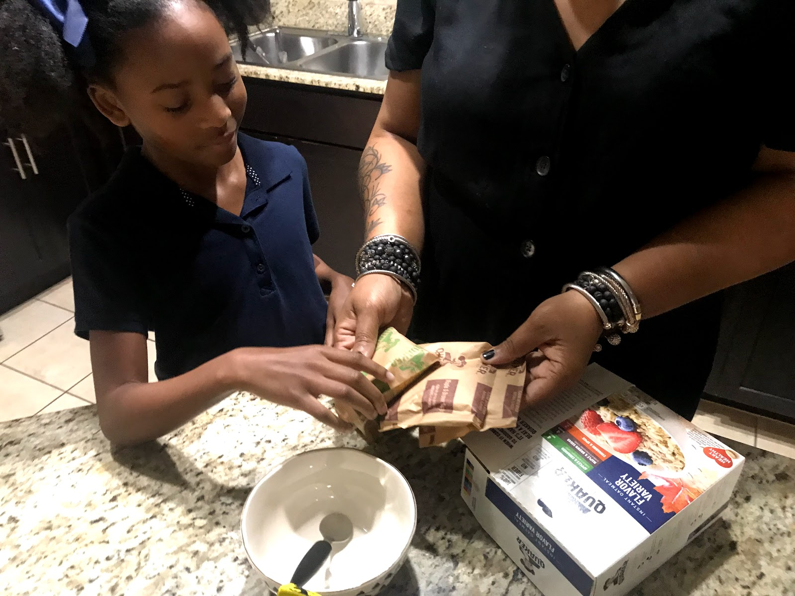 Image: Tangie Bell and Her daughter picking out her favorite oatmeal for breakfast