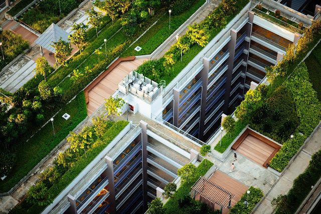 The image shows a modern apartment building which has decking and greenery on the roof. The roof has become a garden area for the local to relax and enjoy. It's a good option for a greener business