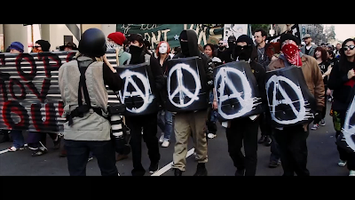 Manifestantes atrás de escudos com símbolo anarquista - Divulgação