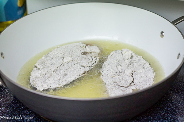 Floured slices of fish in a pot of oil frying