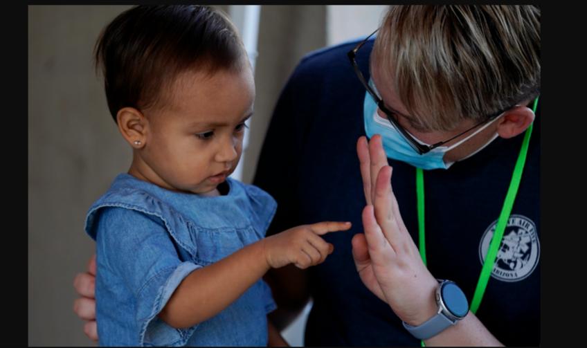 El voluntario Mark McDonald, a la derecha, trabaja con un niño inmigrante en una clínica habilitada para solicitantes de asilo que esperan en Matamoros, México, el jueves 19 de noviembre de 2020 / VOA