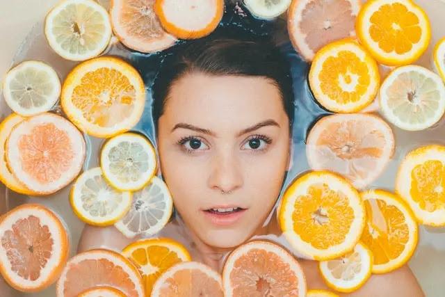 Rostro de una mujer en medio de rebanadas de naranja, limón y toronja sobre el agua
