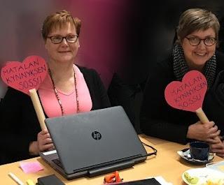 """Seija Okulov ja Anne Tuikka istuvat pöydän ääressä käsissään """"Matalan kynnyksen sossu"""" -kyltit."""