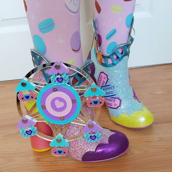 close up of rotating ferris wheel on side of ankle boot with swinging carriages