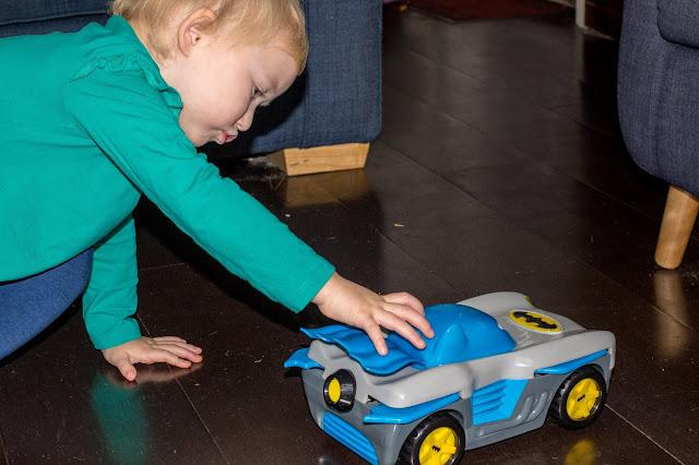 A preschooler pushing the Herodrive Batman Racer toy car to review it