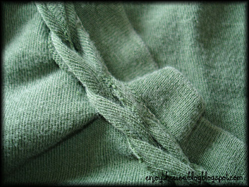 closeup of braided neckline on a green tee