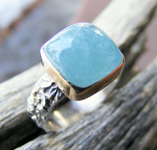 aquamarine gemstone in a gold bezel ring