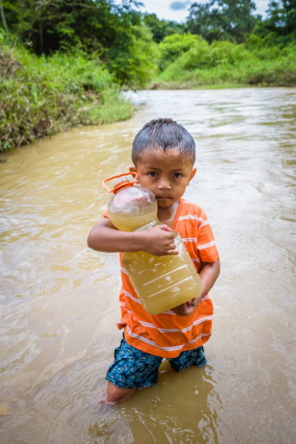 child holding a jug of dirty water