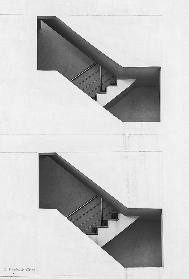 A Black and White Minimalist Photo of Side view of Dual staircase openings in a building.