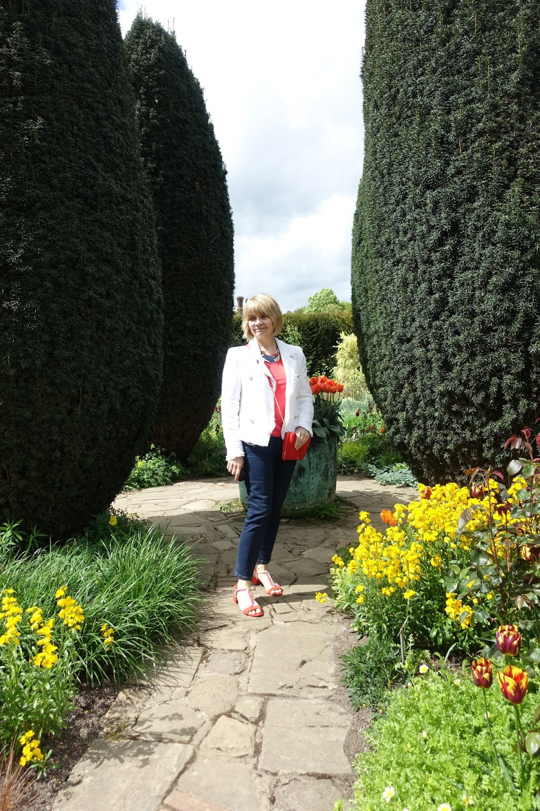 Posing between tall clipped hedges over-50s blogger Gail Hanlon at Sissinghurst