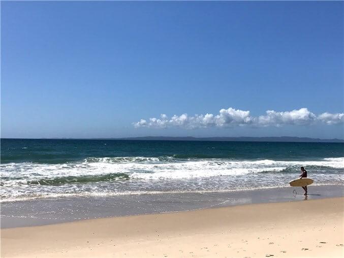 ブライビー島のWoorim Beachでサーフボードもって波を見ている人の写真