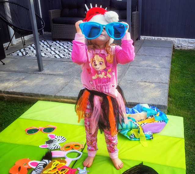 Image of a young girl stood in a garden wearing pink Paw Patrol pyjamas featuring Skye from Paw Patrol as well as wearing giant blue novelty oversized sunglasses, a red velvet santa hat and a spiked flashing headband on top of the hat. Plus a Halloween tutu that is purple, orange and black. On the floor are some green Ikea Plufsig mats with dressing up/ fancy dress items such as animal masks, rabbit ear. oversized sunglasses and beards strewn across the mats.