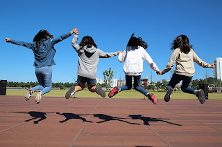 group of girls facing away from the camera, holding hands and jumping