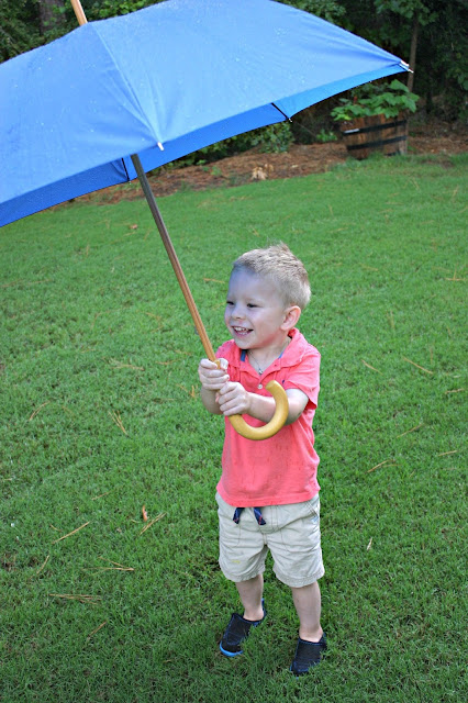 Boy playing with umbrella in the rain