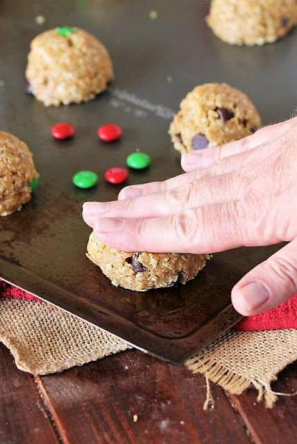 Flattening Christmas Monster Cookie Dough Ball with Hand Image