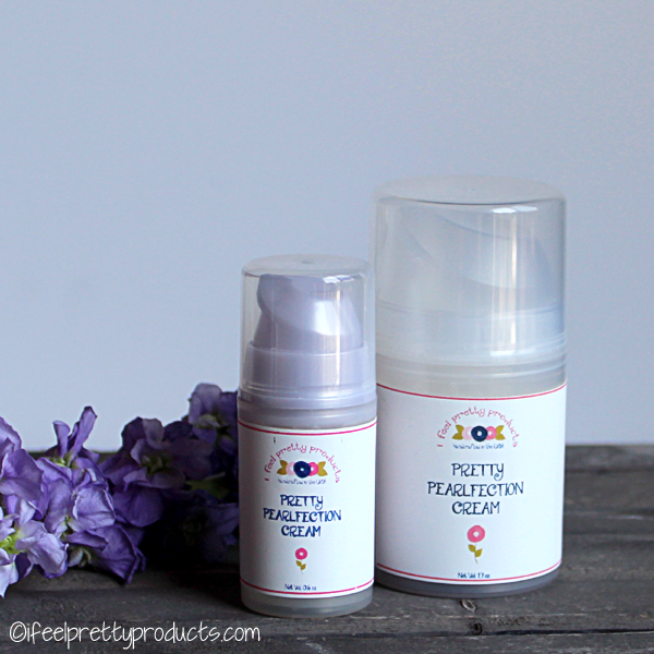 Two different sized bottles of Pretty Pearlfection Cream sitting on a wooden table with purple flowers in the background.