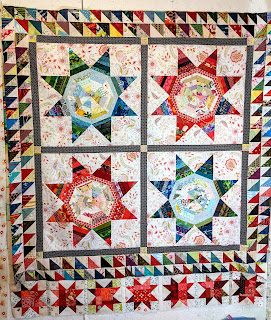 The Sawtooth Stars are added as a row to one end of the LeMoyne Star quilt top