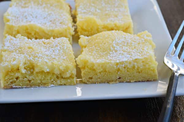 Gooey Lemon Cake Bars - Turn your favorite Gooey Butter Cake into a Lemon dessert! Gooey Lemon Cake Bars will make you quite happy, and nobody has to know you started with a mix!