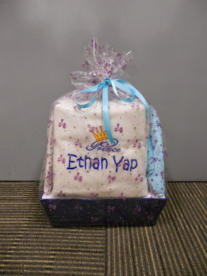 Hamper that contains personalized towels, blanket, and romper