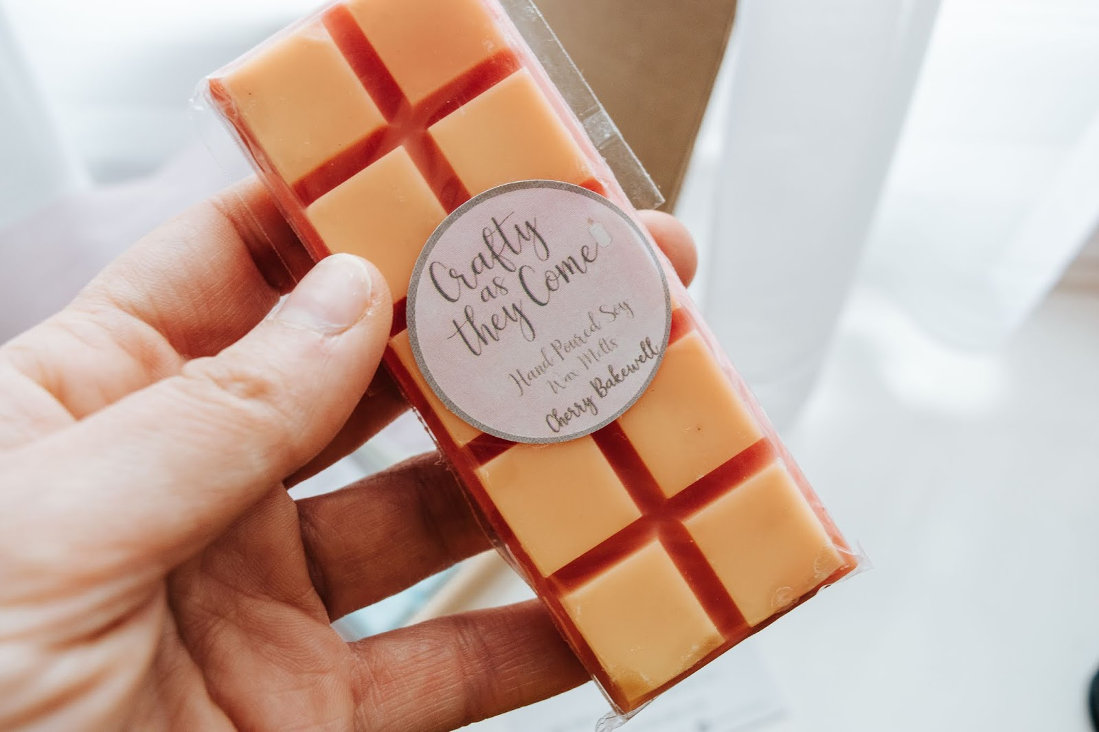 A red and orange Cherry Bakewell scented wax melt bar.