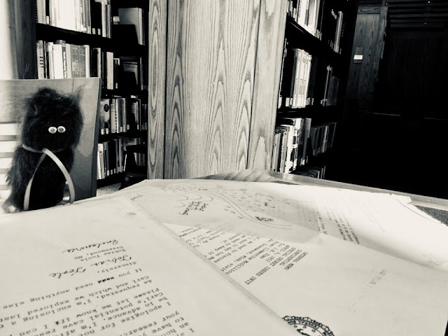 Black and white photo of a fuzzy finger puppet sitting in a chair and looking at documents. Library shelves are behind it.