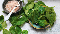 Green spinach leaves next to a bowl of pink salt.
