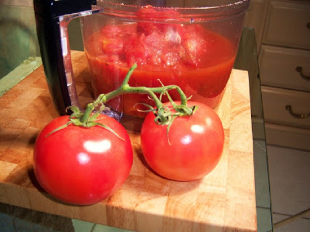 this is a food processor filled with fresh tomatoes pureed